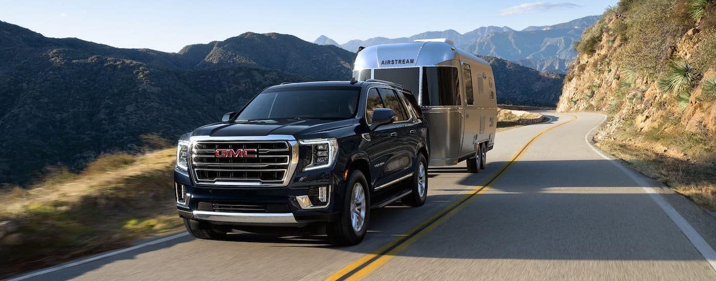 A black 2021 GMC Yukon is towing an Airstream trailer on a highway.