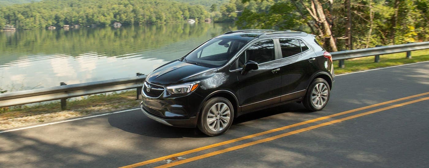 A black 2020 Buick Encore is driving on a highway in front of a lake near Atlanta, GA.