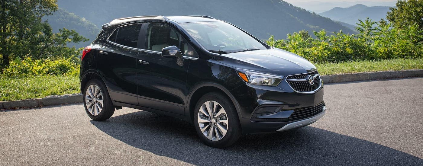 A dark blue 2020 Buick Encore is parked in an empty lot with mountains in the distance.