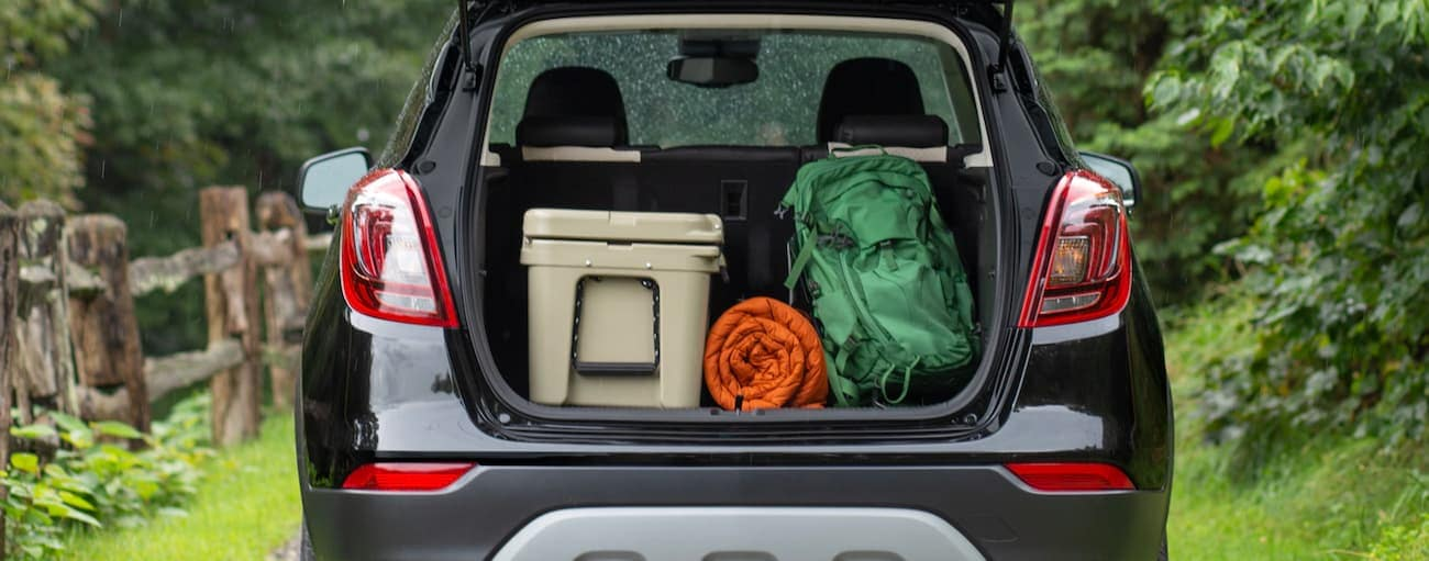 Camping gear is shown in the open cargo area of a 2020 Buick Encore.