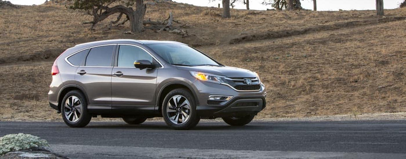 A gray 2015 Honda CR-V is driving on a highway.