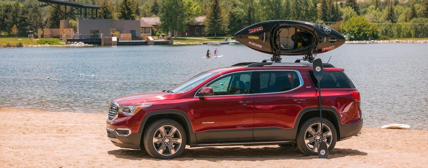A red 2018 GMC Acadia with a kayak on the roof is parked in front of a lake and mountains.