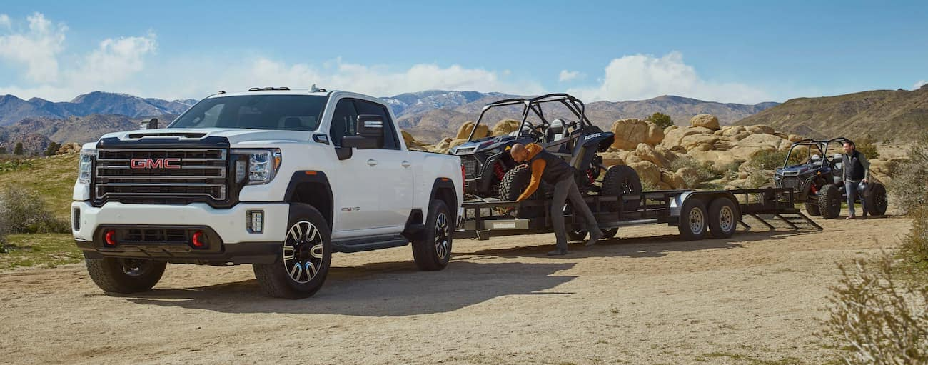 A white 2020 GMC Sierra 2500 AT4 is attached to a trailer that is being loaded with side-by-sides.