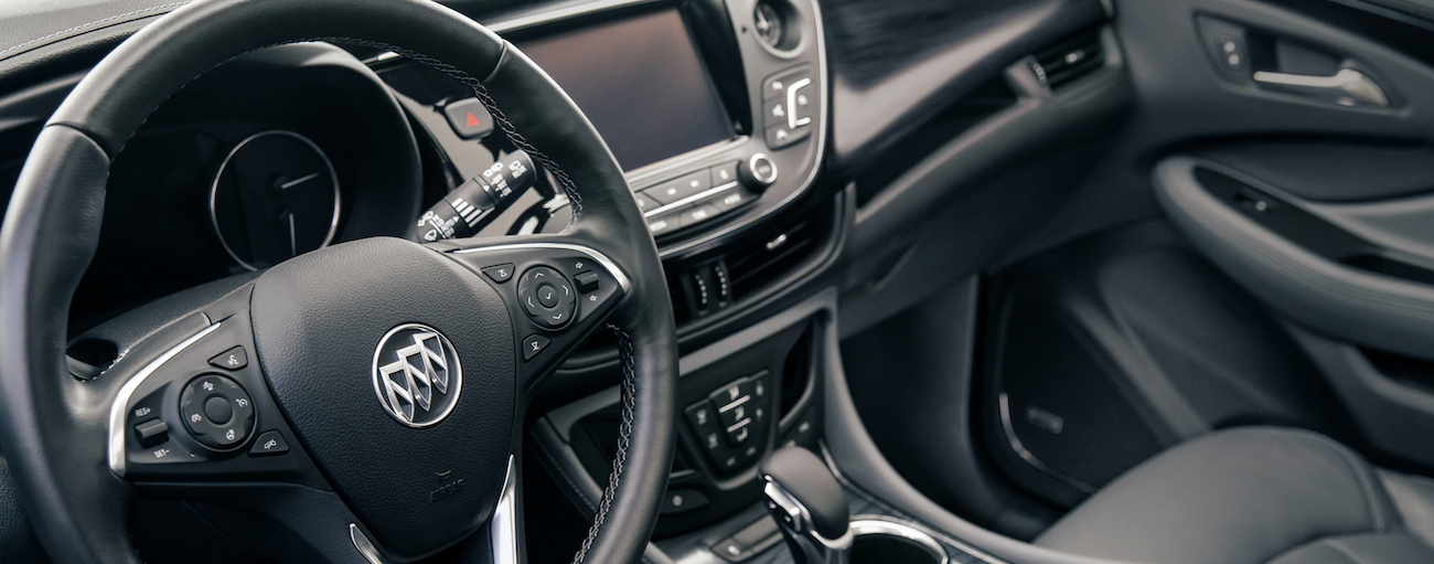 The black interior of a 2020 Buick Envision, similar to the 2021 model, is shown.