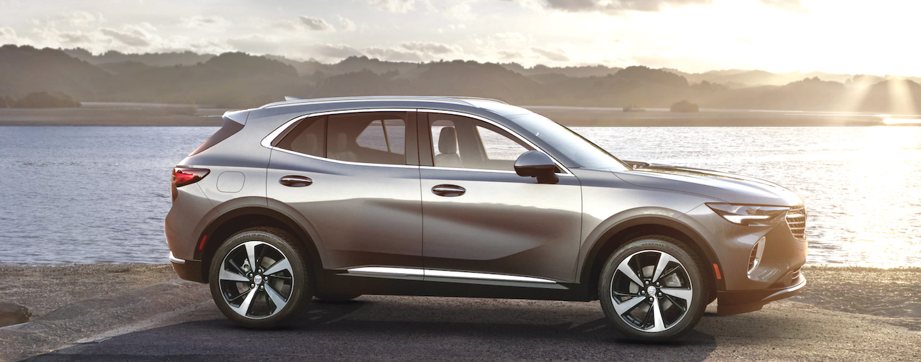 A grey 2021 Buick Envision is facing left while parked in front of a lake.