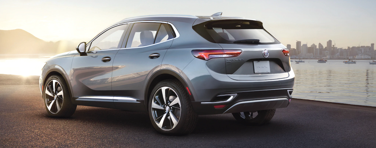 The rear end of grey 2021 Buick Envision is shown in front of a body of water after winning the 2021 Buick Envision vs 2020 Buick Envision comparison.