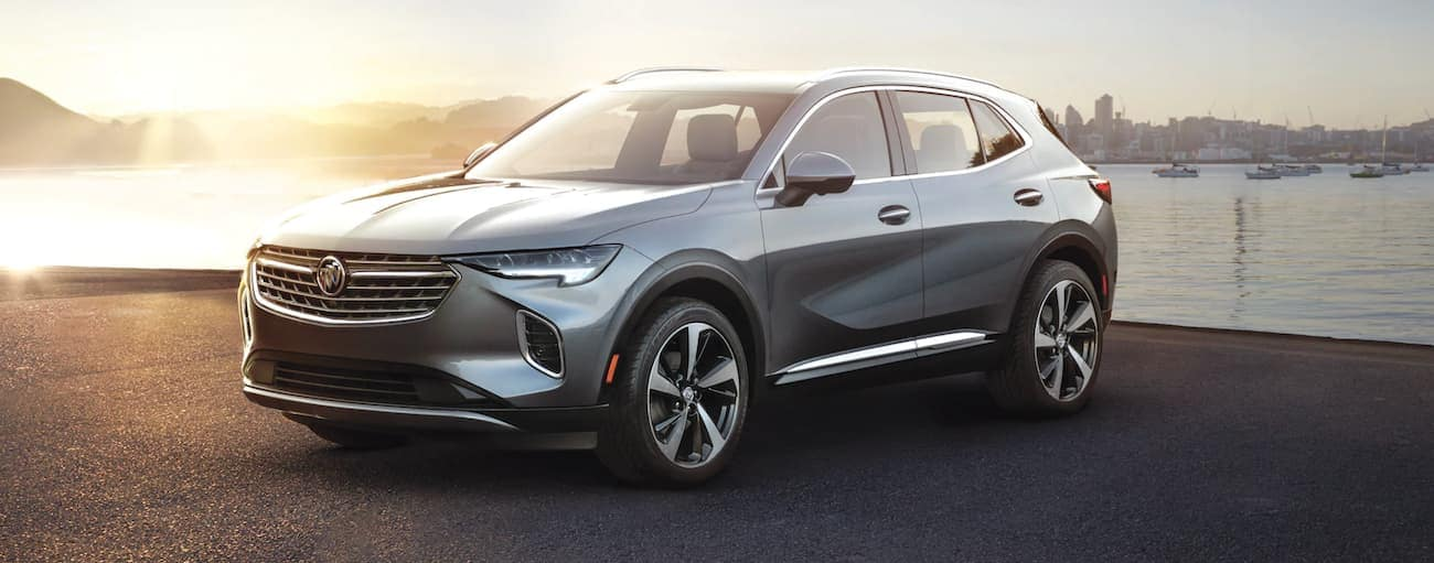 A grey 2021 Buick Envision is parked in front of a body of water at sunset after winning the 2021 Buick Envision vs 2021 Hyundai Santa Fe comparison.