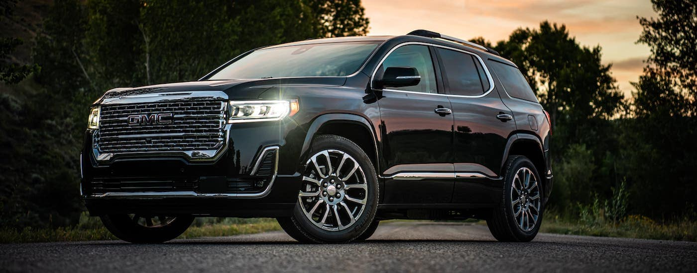 A black 2020 GMC Acadia Denali is parked in front of trees at sunset near Atlanta, GA.