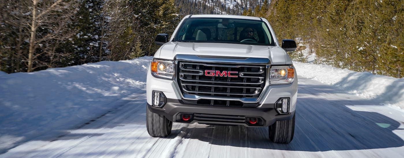A white 2021 GMC Canyon AT4 is shown from the front on a snowy road.