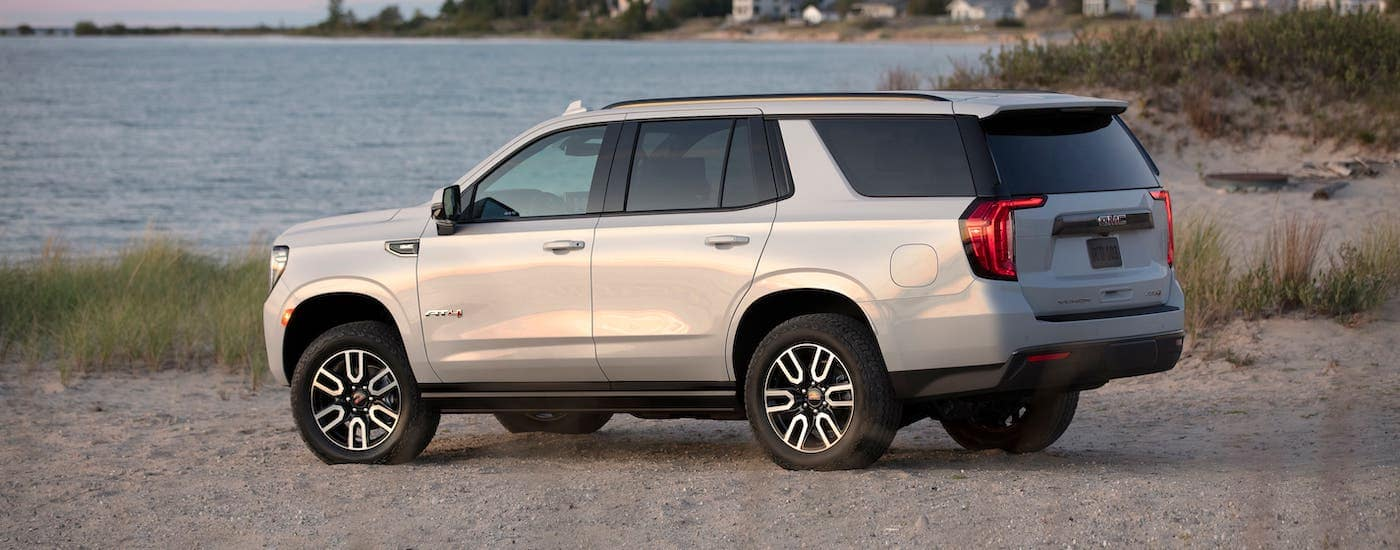 A white 2021 GMC Yukon AT4 from a local GMC dealer is parked on a beach.