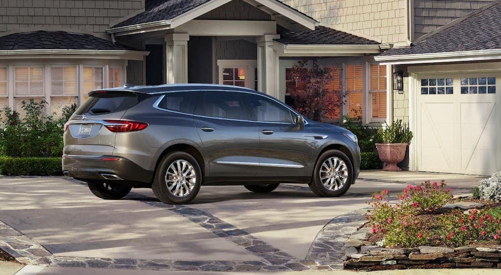 A gray 2019 used Buick Enclave is parked in front of a home.