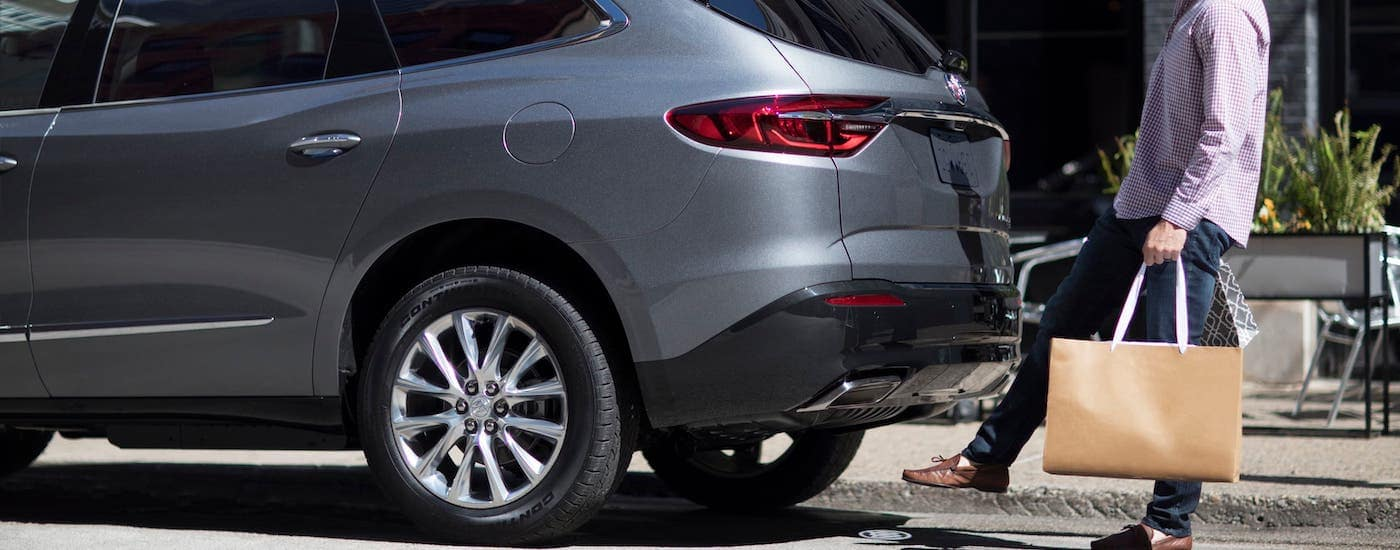 A man is using the foot-activated liftgate on a gray 2019 Buick Enclave on a street near Atlanta, GA.