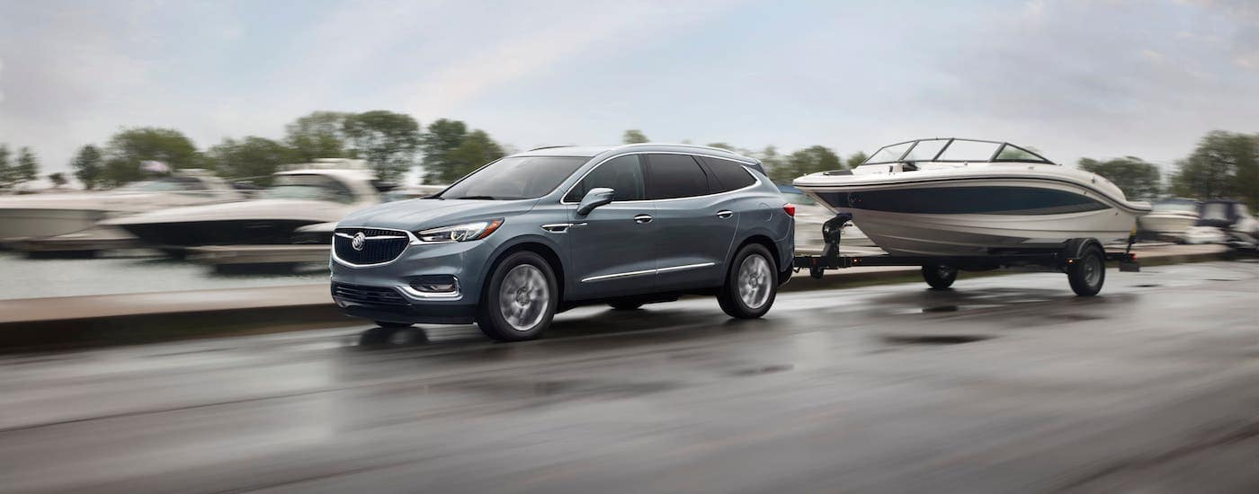 A gray 2019 Buick Enclave is towing a boat on a highway.