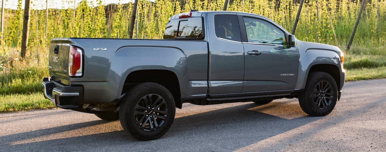 A grey 2020 GMC Canyon is shown from the rear-side angle in front of trees and tall grass near Buford, GA.