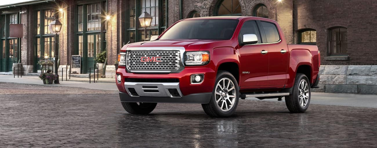 A red 2020 GMC Canyon is parked in front of a brick building after winning the 2020 GMC Canyon vs 2020 Chevy Colorado comparison.
