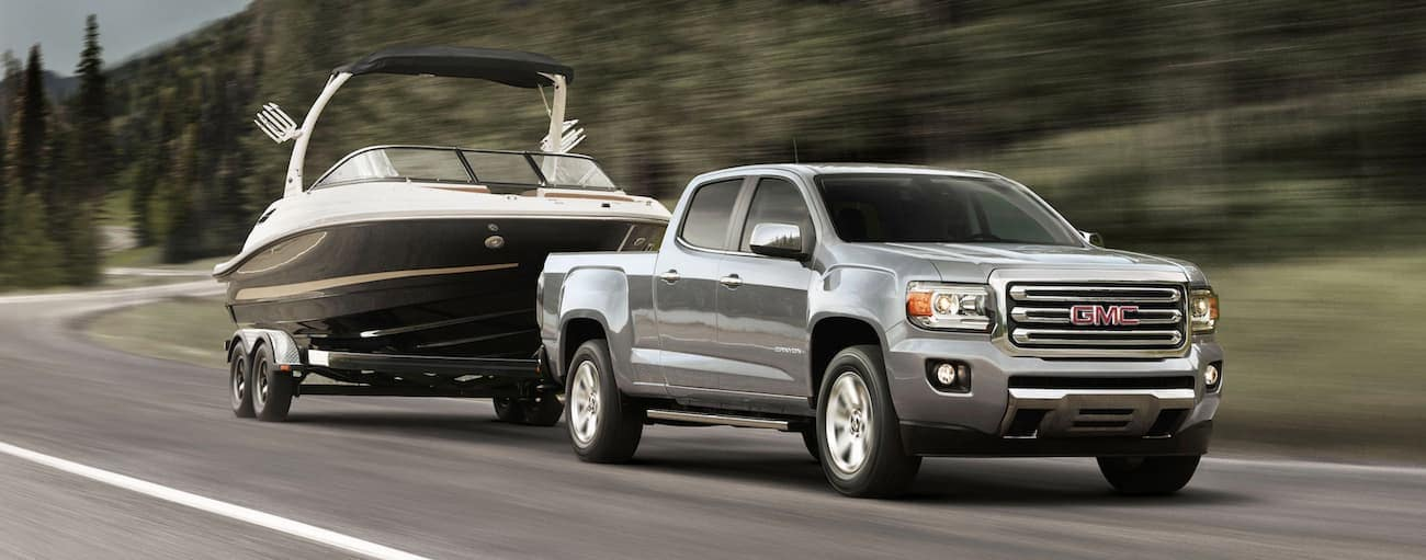 A silver 2020 GMC Canyon is towing a boat past trees near Buford, GA.