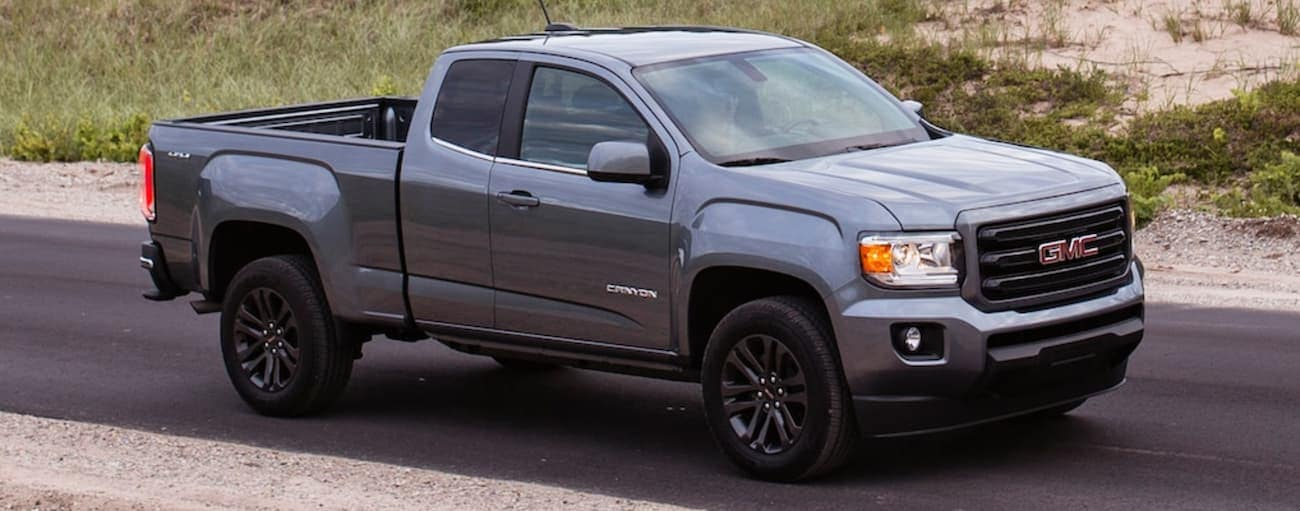 A grey 2020 GMC Canyon is driving on a rural road past grass and sand outside of Atlanta, GA.