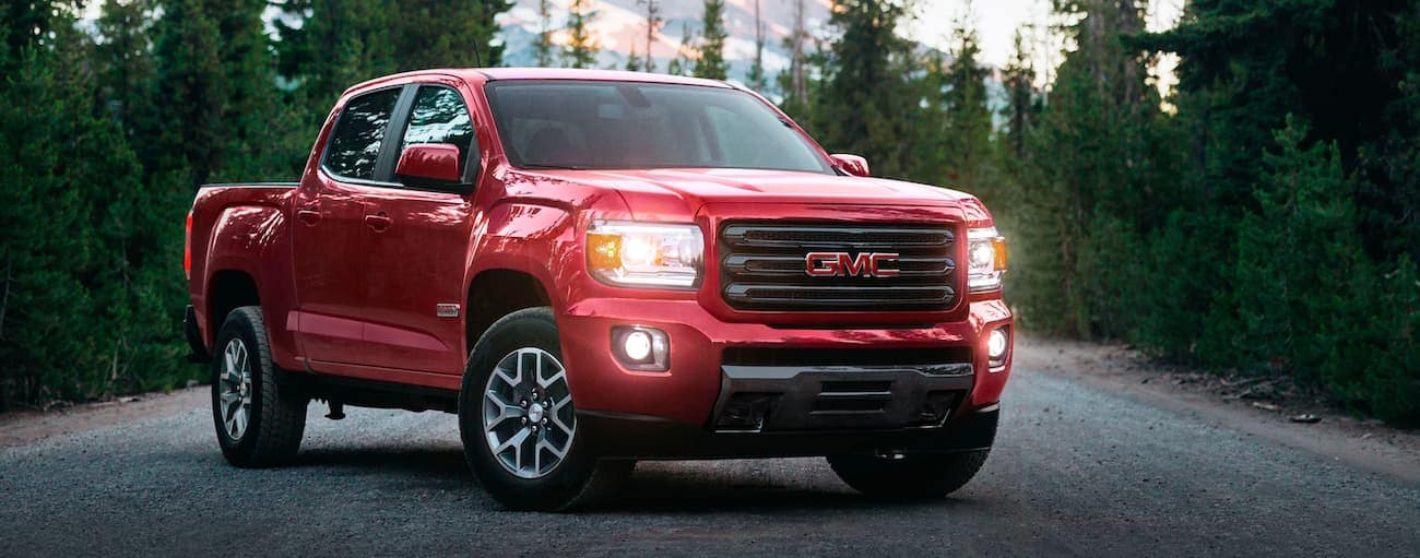 A red 2020 GMC Canyon is parked in front of pine trees after winning the 2020 GMC Canyon vs 2020 Nissan Frontier comparison.