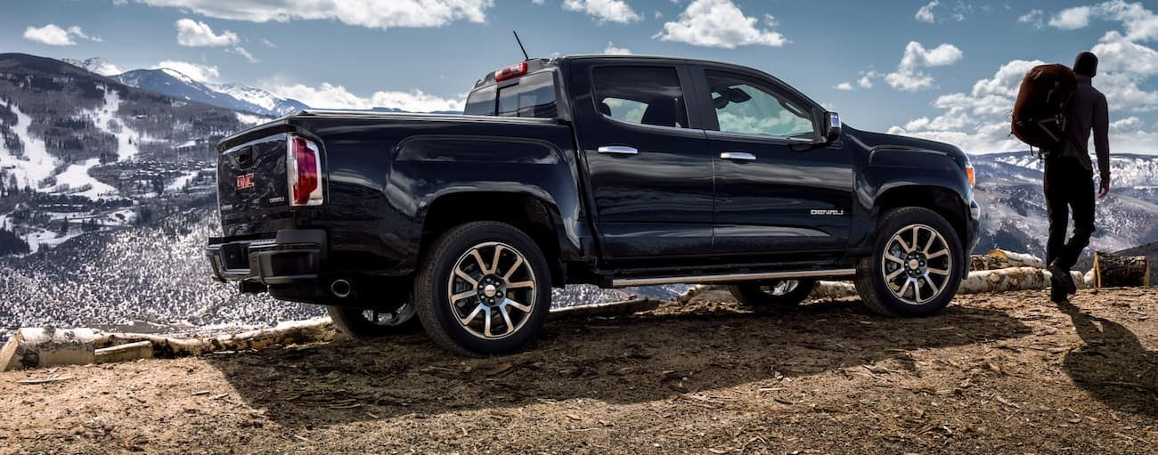 A man is walking away from a black 2020 GMC Canyon parked in front of mountains.