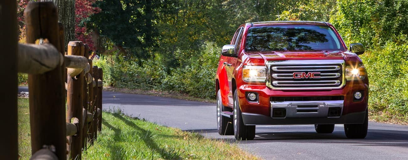A red 2020 GMC Canyon is driving past a fence on a rural road outside of Atlanta, GA, after winning the 2020 GMC Canyon vs 2020 Toyota Tacoma comparison.