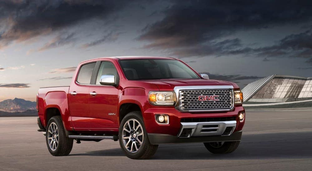 A red 2020 GMC Canyon Denali from a local GMC dealer is parked in front of a glass building at dusk.