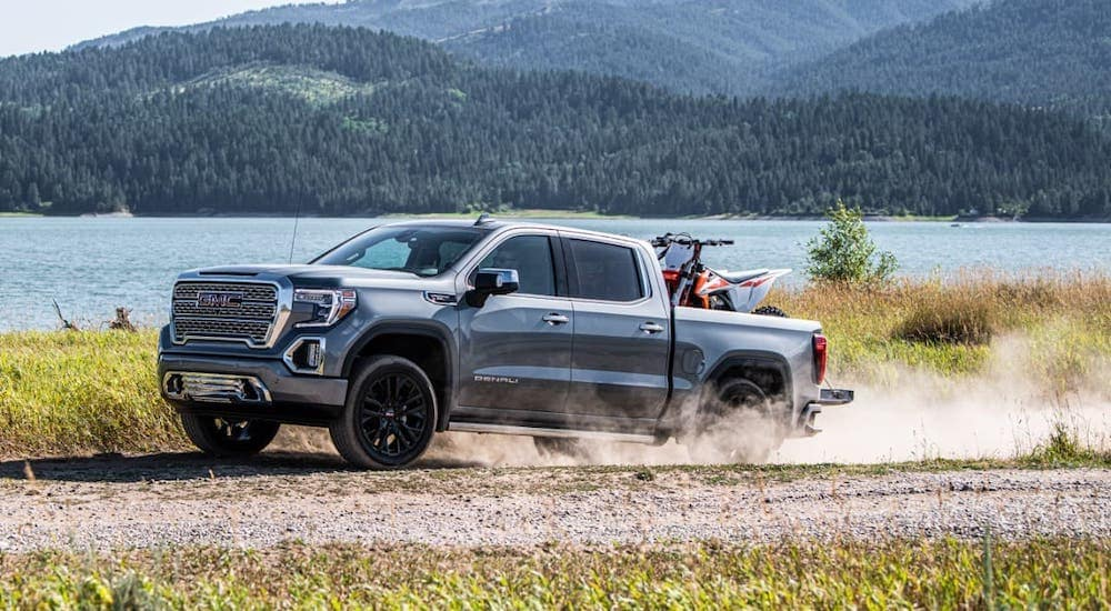 A silver 2020 GMC Sierra Denali with a dirt bike in the bed is kicking up dirt on a dirt road next to a river.
