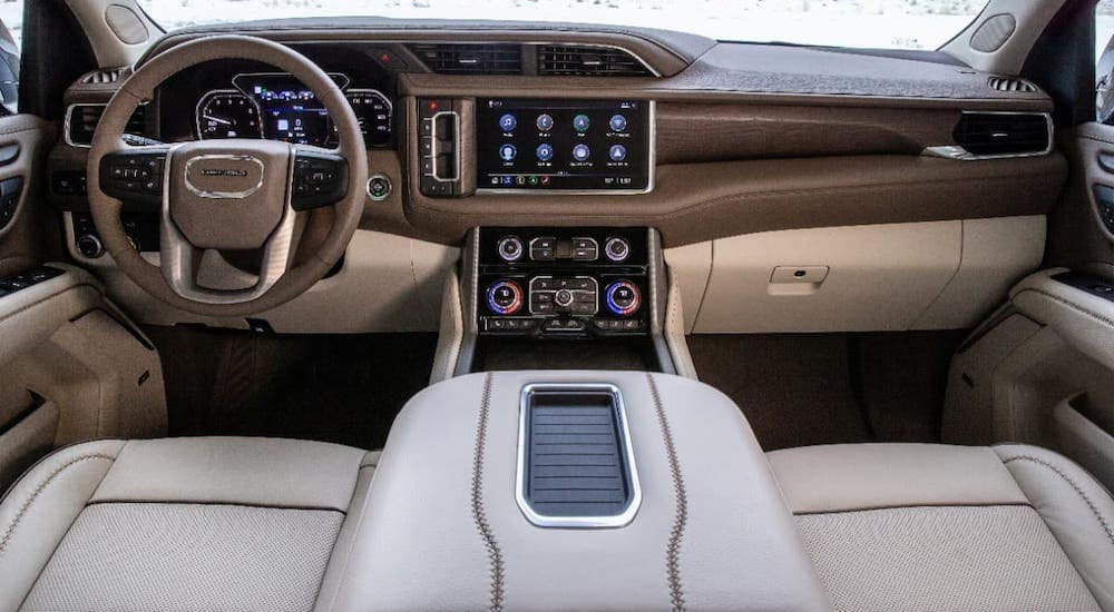 The brown and tan front seats and dashboard of a 2021 GMC Yukon Denali are shown.