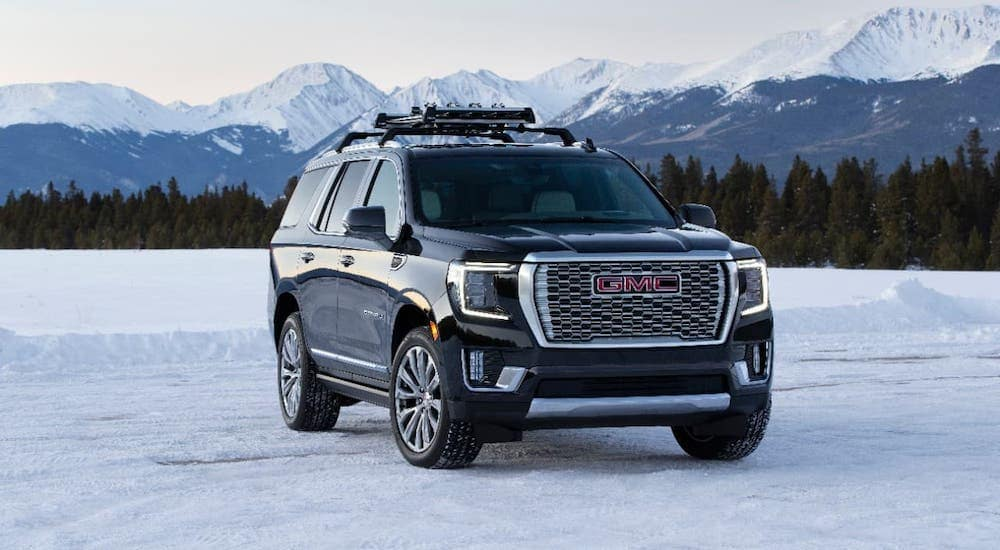 A black 2021 GMC Yukon Denali from a local GMC dealer is parked on a snowy field in front of snow-covered mountains.