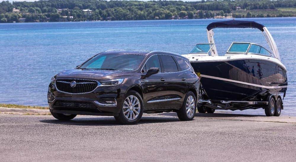 A black 2019 Buick Enclave is towing a boat away from a lake.