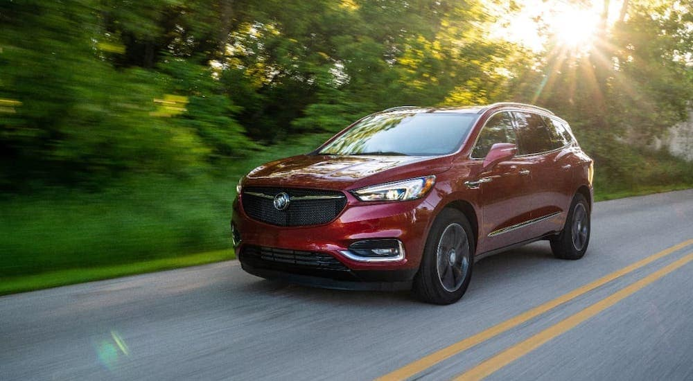A red 2019 used Buick Enclave Sport Touring is driving on a rural road near Atlanta, GA.