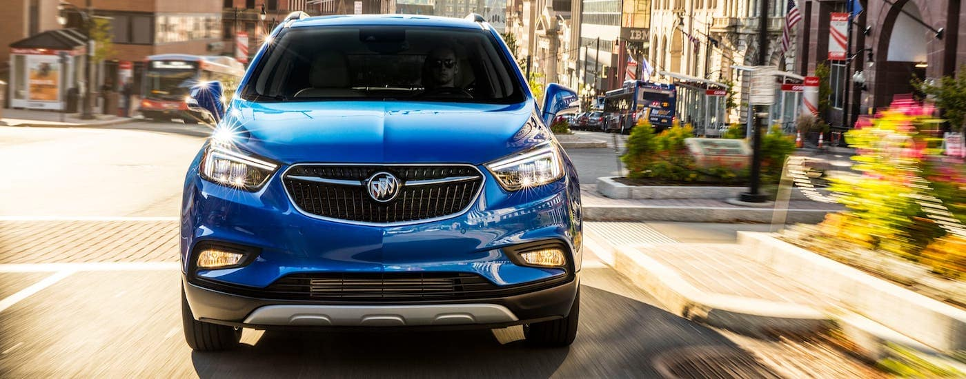 A blue 2021 Buick Encore is shown from the front while driving on a city street.