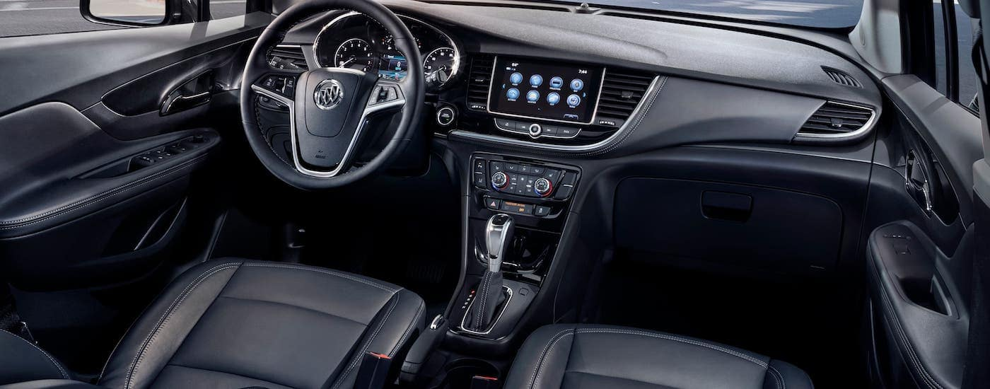 The black front seats and dashboard are shown in a 2021 Buick Encore.