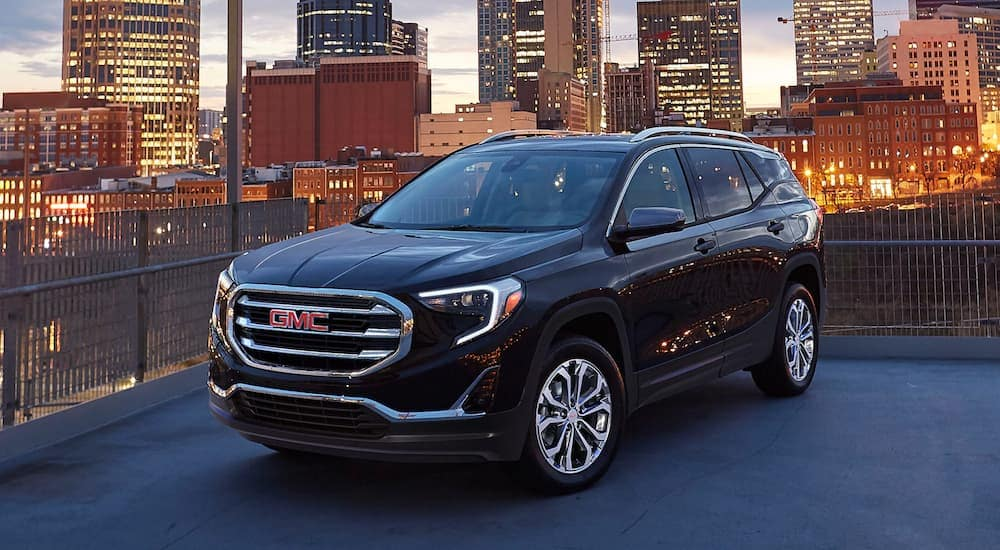 A black 2020 GMC Terrain SLE is on top of a parking garage overlooking the city after leaving a Atlanta GMC dealer.