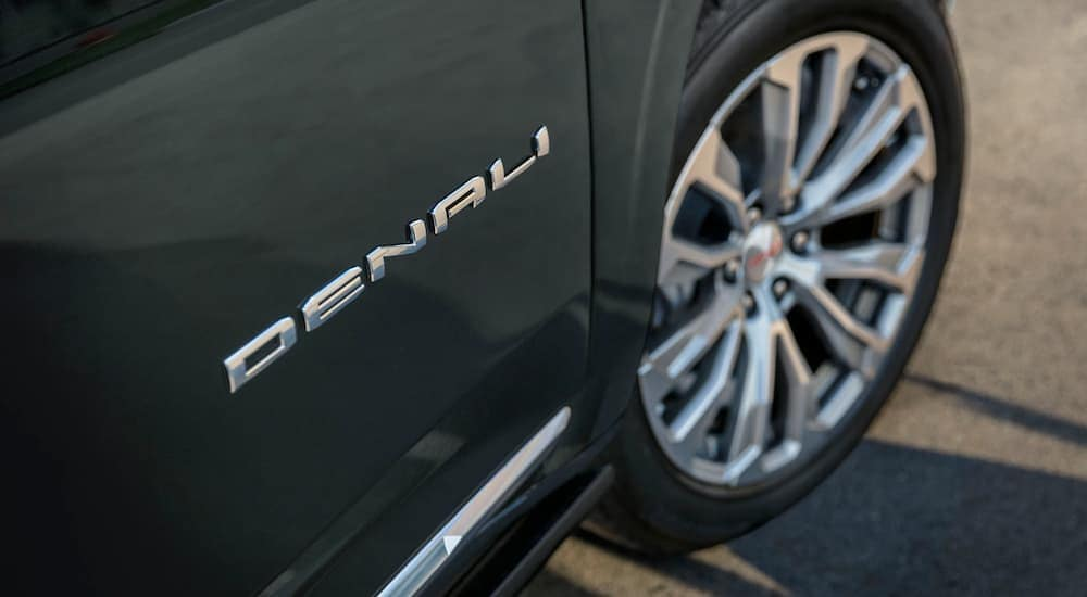 A dark grey 2021 GMC Yukon Denali is shown with a close up on the Denali badging on the door.