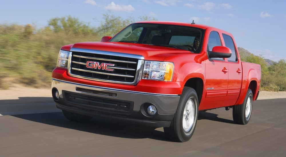 A red 2013 used GMC Sierra 1500 SLT is driving down the road.