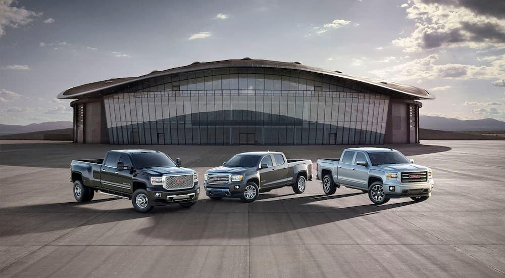 A silver 2015 used GMC Canyon, a grey 2014 used GMC Sierra 1500, and a grey 2015 used GMC Sierra Denali 3500 HD are parked in front of a glass faced building.