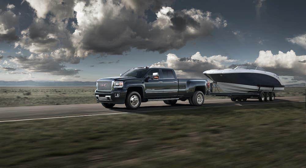 A blue 2016 used GMC Sierra 3500 HD Denali is towing a boat past a field.