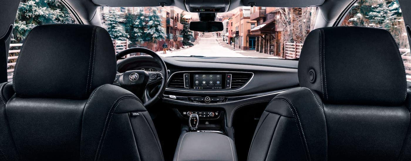 The black leather interior and dashboard of a 2021 Buick Enclave is shown from the rear seat.