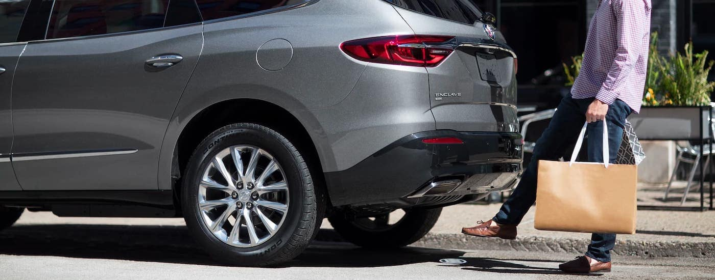 A man is using his foot to open the liftgate on a silver 2021 Buick Enclave.
