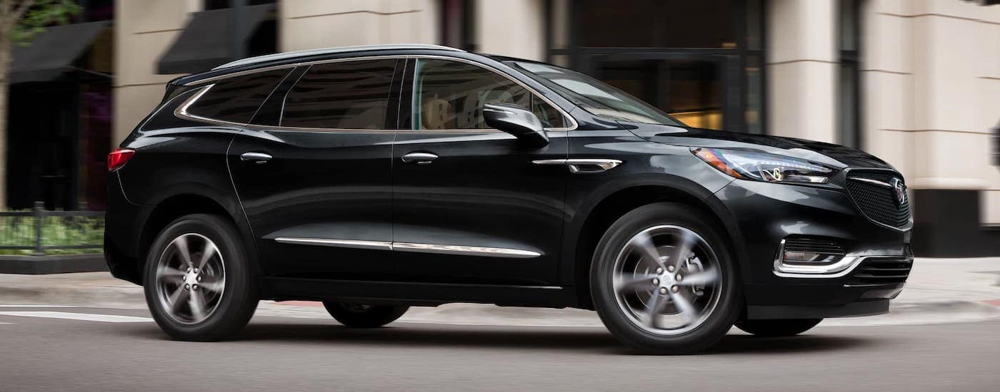 A black 2021 Buick Enclave is driving on a city street after winning the 2021 Buick Enclave vs 2021 Volvo XC90 comparison.