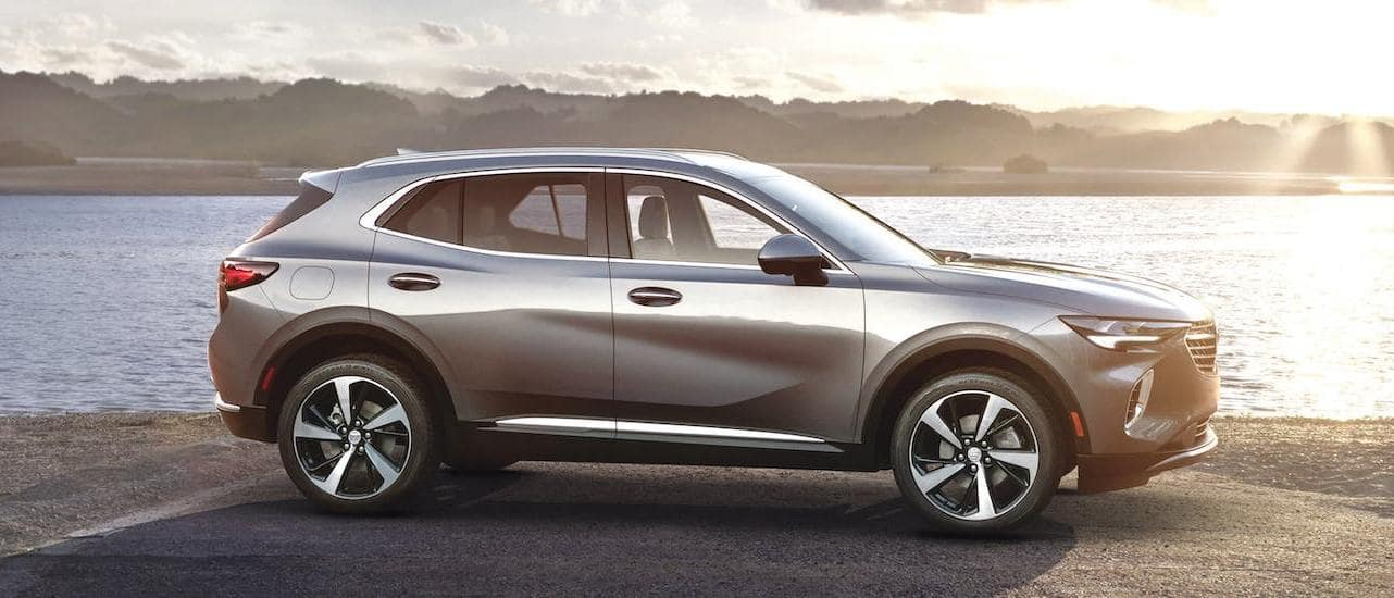 A silver 2021 Buick Envision is shown from the side while parked in front of a river.
