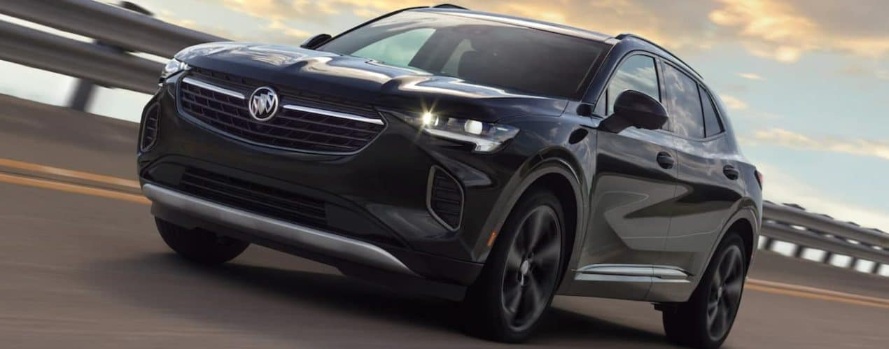 A black 2021 Buick Envision is driving on a highway after winning the 2021 Buick Envision vs 2021 Acura RDX comparison.