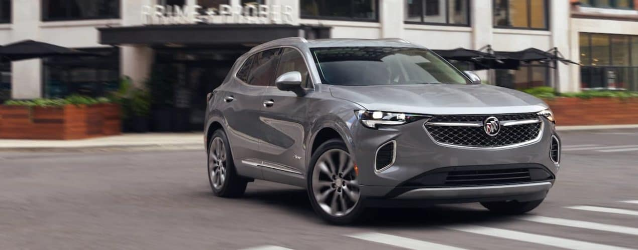 A grey 2021 Buick Envision is driving through an intersection on a city street.