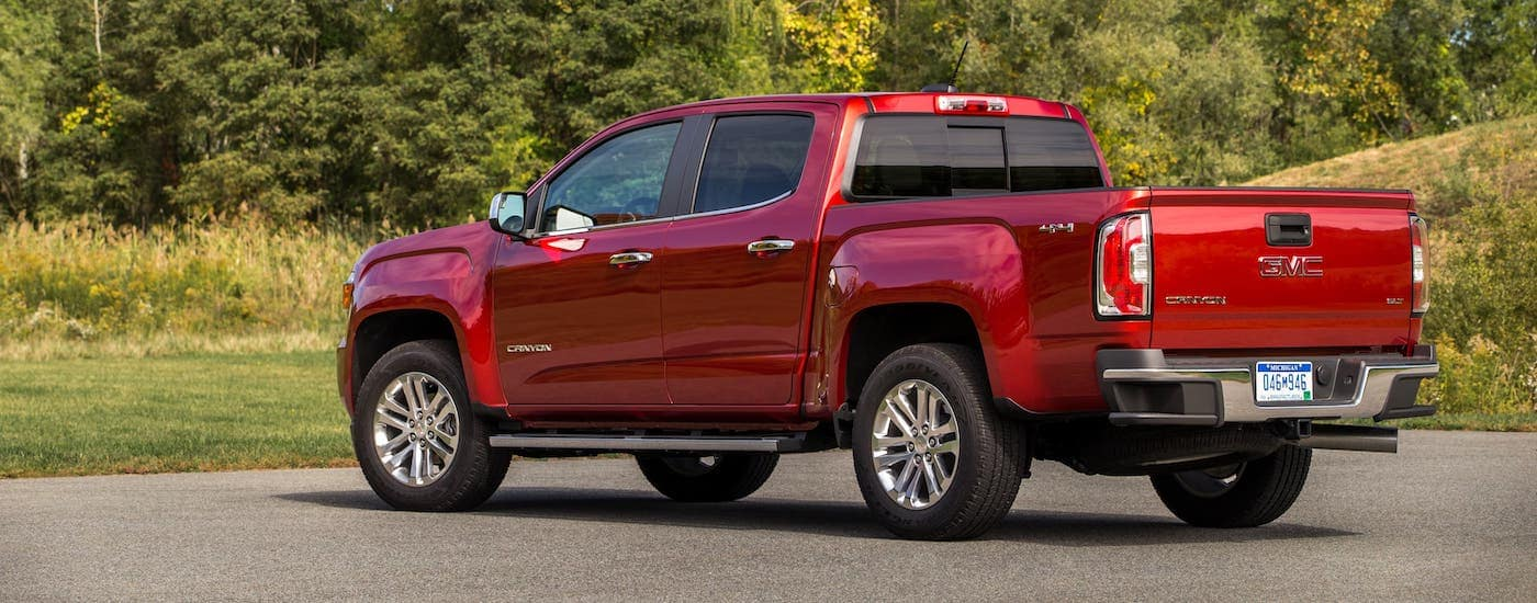 A red 2021 GMC Canyon SLT diesel is shown parked in front of trees.