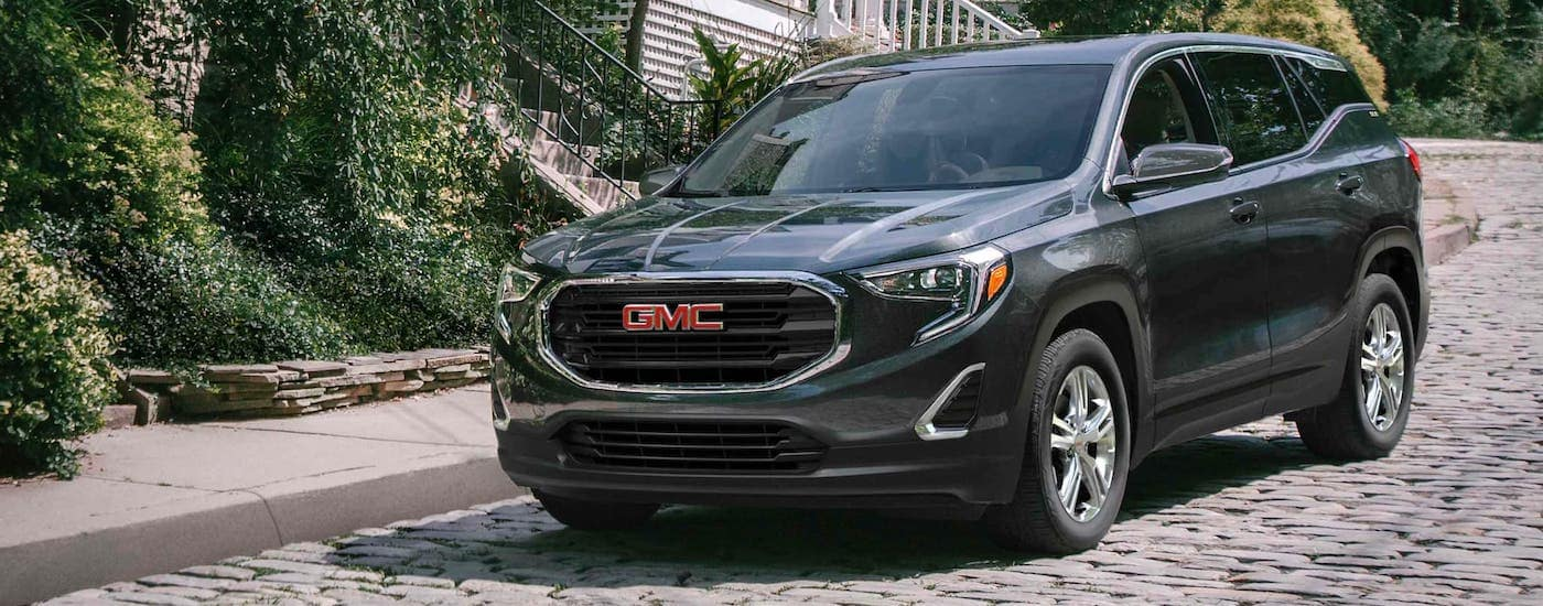 A black 2021 GMC Terrain is parked on a cobblestone road.
