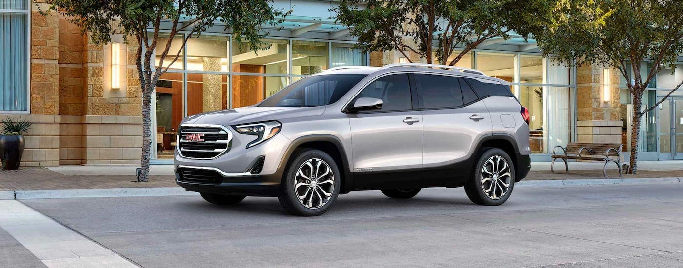 A silver 2021 GMC Terrain is parked on a city street after winning the 2021 GMC Terrain vs 2021 Honda CR-V comparison.