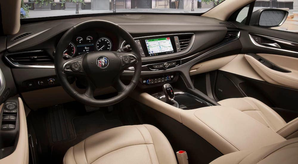 The black and tan interior and dashboard of a 2020 Buick Enclave are shown.