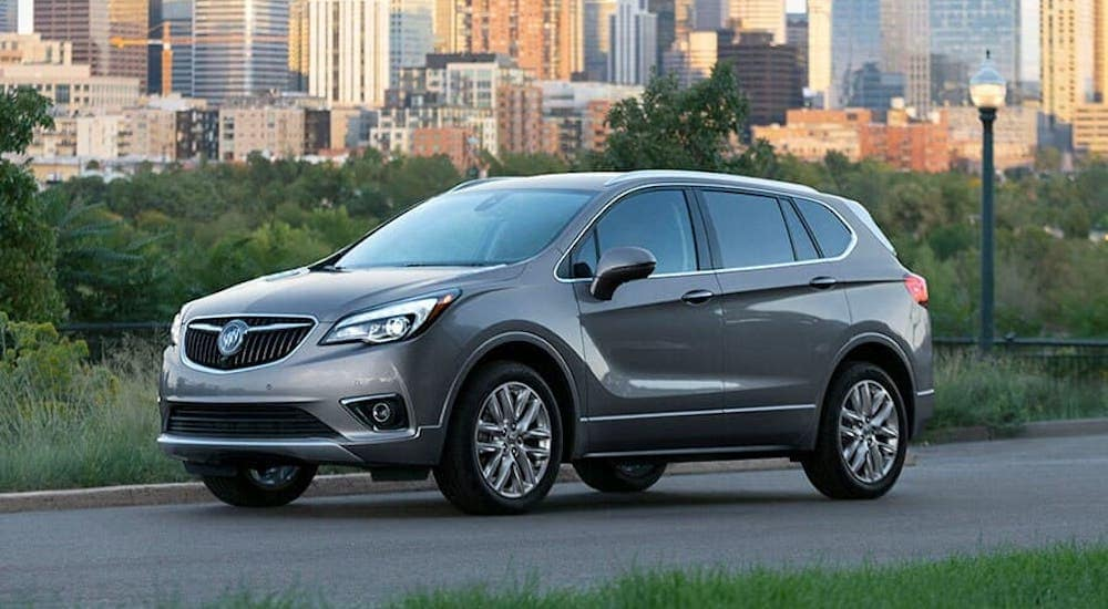 A gray 2020 Buick Envision is parked on a street with a city in the distance.