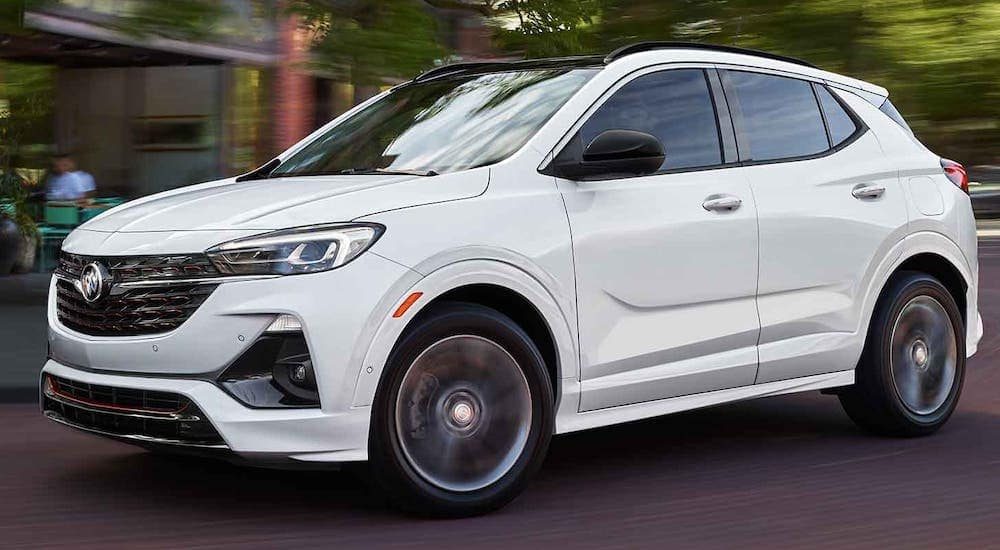 A white 2021 Buick Encore GX is driving on a city street after leaving an Atlanta Buick dealer.