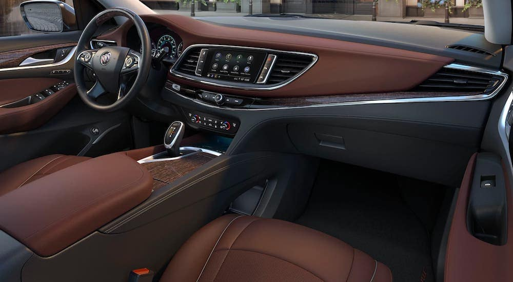 The luxurious brown and black leather interior of a used 2020 Buick Enclave Avenir is shown.